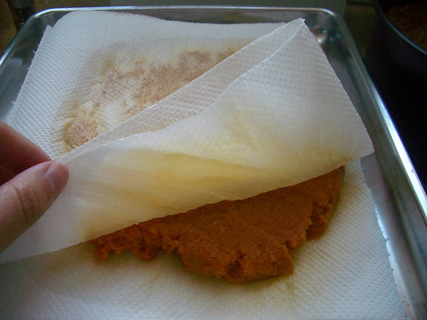 blotting canned pumpkin on paper towels to absorb excess moisture